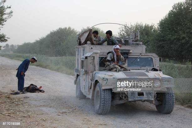 Graphic content / This photo taken on July 17 2017 shows Afghan security personnel riding in a Humvee as an man inspects the body of a suspected...