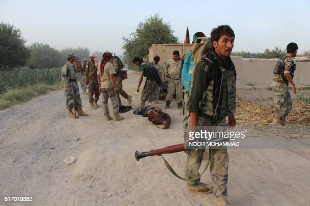 Graphic content / This photo taken on July 17 2017 shows Afghan security personnel gathered around the body of a suspected Taliban militant after he...