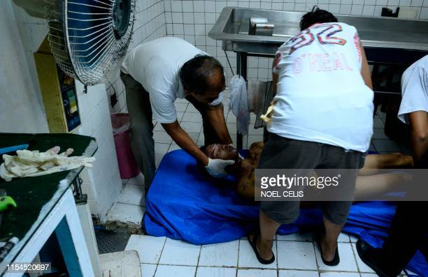Graphic content / This photo taken on July 6 shows funeral workers at the morgue handling the body of Ricky Adarayan who was abducted on July 4 and...