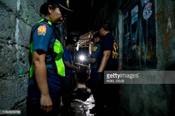Graphic content / This photo taken on June 27 shows policemen at the crime scene where the body of a barangay health worker and former drug...