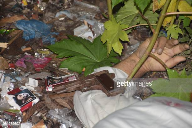 Graphic content / This photo taken on May 18 2018 shows a gun next to the dead body of a Bangladeshi alleged drug dealer after a gun battle with law...