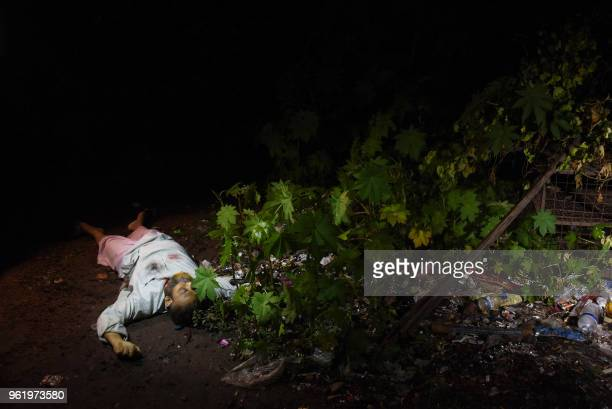 Graphic content / This photo taken on May 18 2018 shows the dead body of a Bangladeshi alleged drug dealer after a gun battle with law enforcement in...