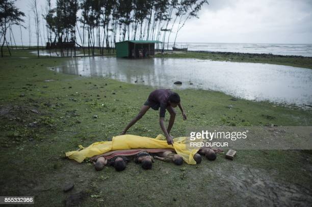 Graphic content / This photo taken on September 28 2017 shows a man covering the bodies of Rohingya Muslim refugee children lined up near the shore...