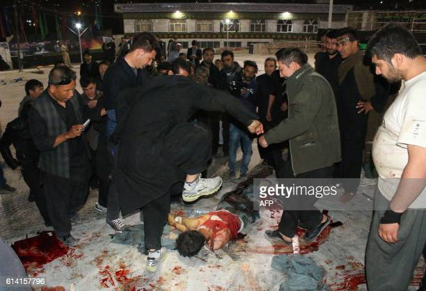 Graphic content / This photograph taken late on October 11 2016 shows an Afghan man kicking the body of an attacker who had shot worshippers at the...