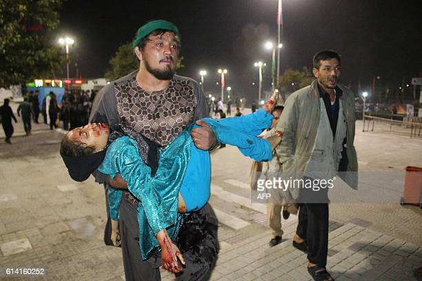 Graphic content / This photograph taken late on October 11 2016 shows an Afghan man carrying a wounded girl after an attack by gunmen at the Karte...