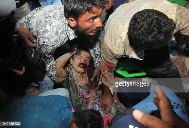 Graphic content / This photograph taken on March 31 2018 shows Indian residents recovering the body of a woman during rescue operations after a...