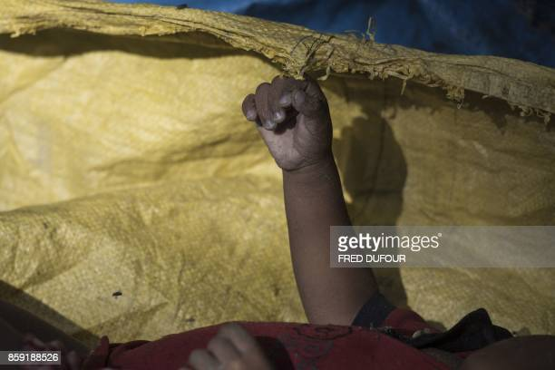 Graphic content / This picture shows the arm of a dead Rohingya Muslim child refugee at Shah Porir Dwip Island on October 9 after a boat capsizing...