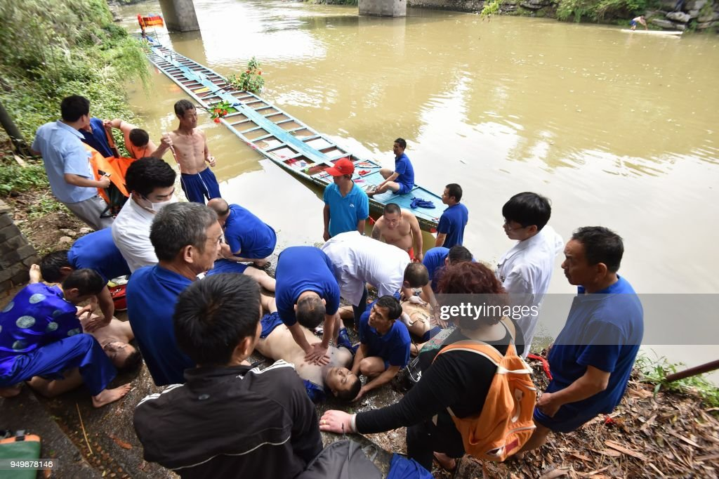 Graphic content / This picture taken on April 21, 2018 shows rescuers giving emergency care to victims of an accident involving two boats capsizing in Guilin in southern China. - Seventeen people were killed on April 21 after two dragon boats capsized in southern China, state-run Xinhua news agency said. Rowers on board the two long, narrow kayak-like boats were practising for a race in Taohua River in the city of Guilin when the accident occurred Saturday afternoon, tipping some 60 people into the water. (Photo by - / AFP) / China OUT