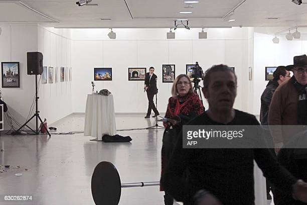 Graphic content / This picture taken on December 19 2016 in Ankara shows guests leaving a gallery as Mevlut Mert Altintas holds a weapon during an...