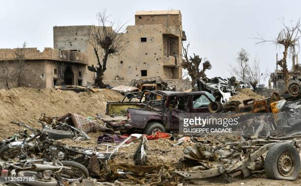 Graphic content / This picture taken on March 24 2019 shows destroyed vehicles and damaged buildings in the village of Baghouz in Syria's eastern...