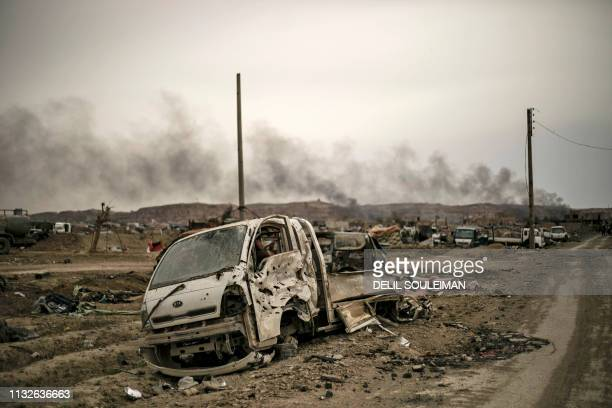 Graphic content / This picture taken on March 24 2019 shows smoke rising behind destroyed vehicles and damaged buildings in the village of Baghouz in...