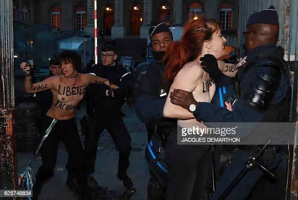 """Graphic content / Topless Femen activists with paint on their body reading """"release Jacqueline """" are detained by French police officers outside the..."""