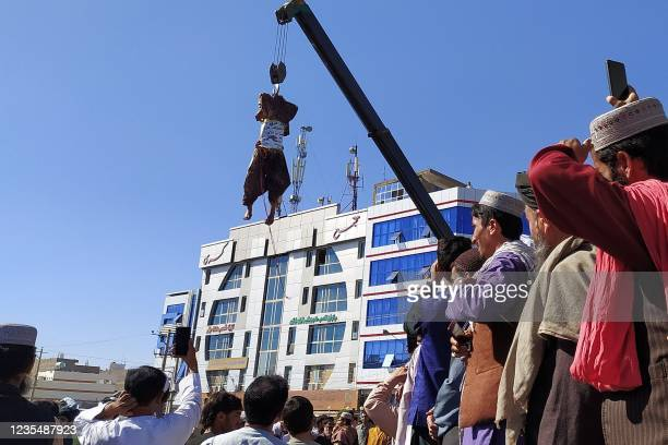 Graphic content / TOPSHOT - A dead body displayed in a public area is hanging on a crane in Herat on September 25 after Taliban killed four...