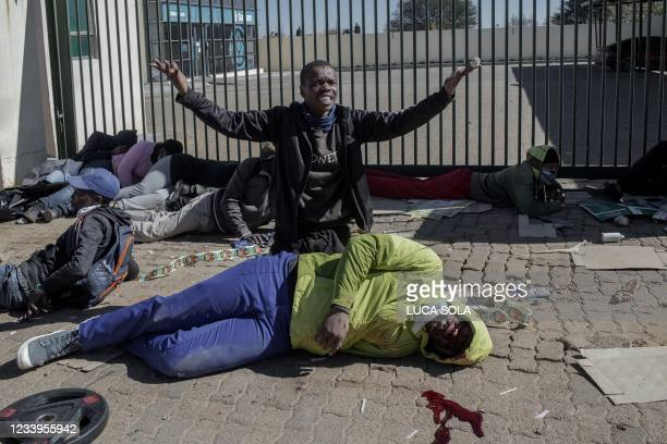 Graphic content / TOPSHOT - A suspected looter gestures to unseen South Africa National Defence Force soldiers asking help for a man who was...