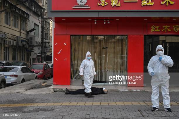 Graphic content / This photo taken on January 30 2020 shows officials in protective suits checking on an elderly man wearing a facemask who collapsed...