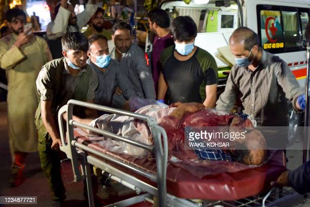 Graphic content / TOPSHOT - Volunteers and medical staff bring an injured man for treatment after two powerful explosions, which killed at least six...