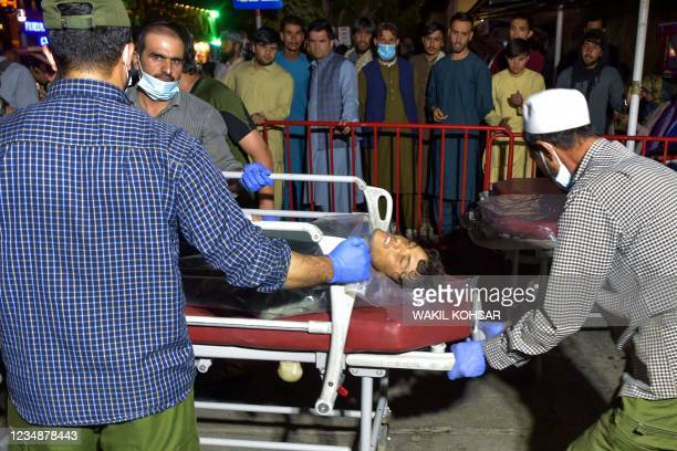 Graphic content / TOPSHOT - Volunteers and medical staff bring an injured man on a stretcher to a hospital for treatment after two powerful...