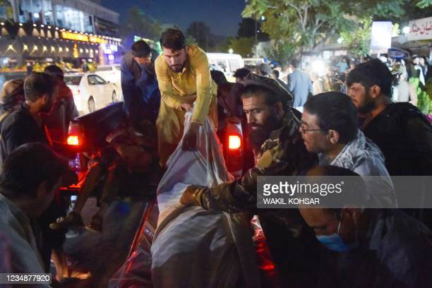 Graphic content / TOPSHOT - Volunteers and medical staff unload bodies from a pickup truck outside a hospital after two powerful explosions, which...