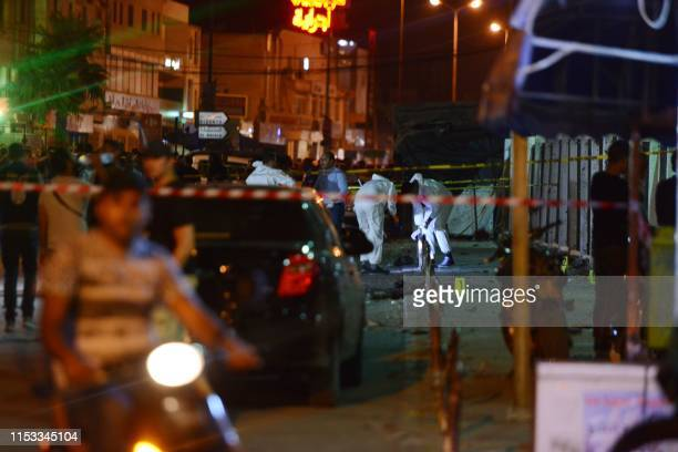 Graphic content / Tunisian explosive experts inspect the scene outside a metro station near the bus stop where a man reportedly wearing an explosive...