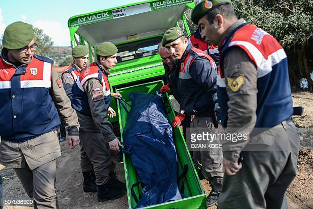 Graphic content / Turkish gendarmes carry the body of a migrant on a beach in Canakkale's Bademli district on January 30 2016 after at least 33...