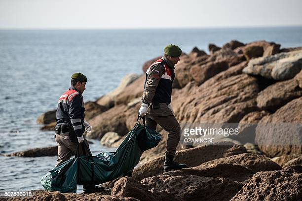 Graphic content / Turkish gendarmes carry the body of a migrant who washed up on a beach in Canakkale's Bademli district on January 30 2016 after at...
