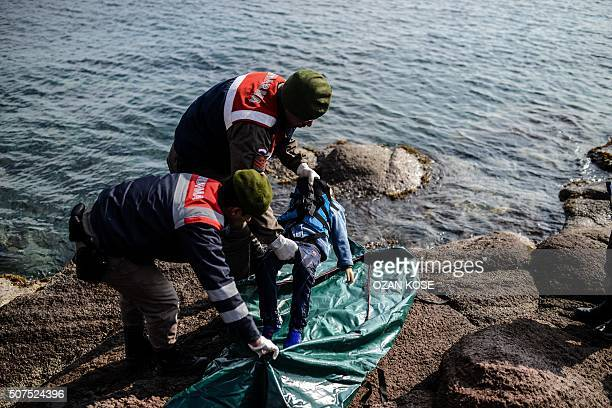 Graphic content / Turkish gendarmes put the body of a child into a body bag on a beach in Canakkale's Bademli district on January 30 2016 after at...