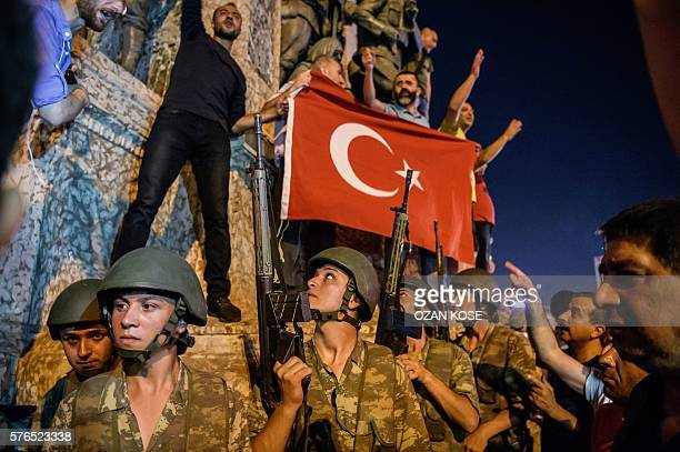 Graphic content / Turkish solders stay with weapons at Taksim square as people protest against the military coup in Istanbul on July 16 2016 Turkish...