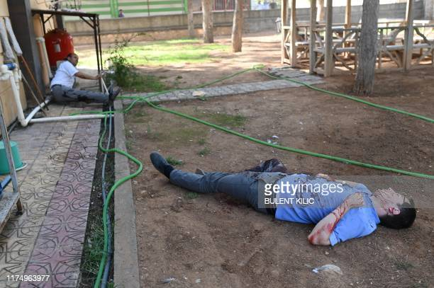 Graphic content / Two injured officers lie on the ground in the garden of a Turkish government building in Akcakale near the Turkish border with...