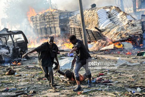 Graphic content / Two men carry the body of a victim following the explosion of a truck bomb in the centre of Mogadishu on October 14 2017 A truck...