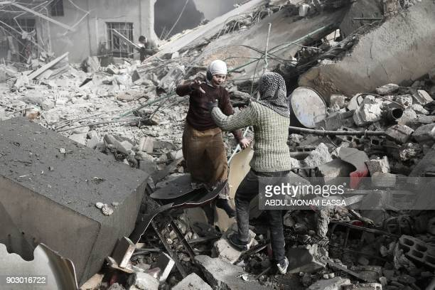 Graphic content / Two Syrian sisters run across the rubble to embrace after finding each other alive following an air strike on Hamouria in the...