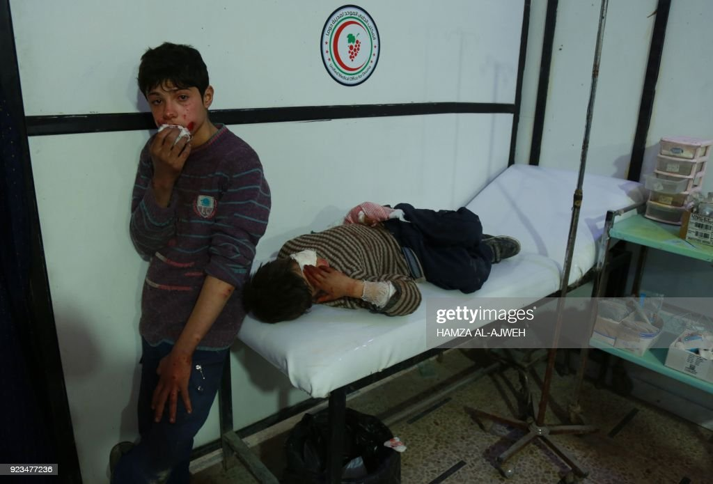 Graphic content / Two wounded Syrian boys wait for medical help at a makeshift hospital following air strikes by regime forces in the rebel-held town of Douma, in the besieged Eastern Ghouta region on the outskirts of the capital Damascus, on February 23, 2018. Syrian regime air strikes and artillery fire hit the rebel-held enclave of Eastern Ghouta for a sixth straight day killing dozens of civilians, as the world struggled to reach a deal to stop the carnage. /