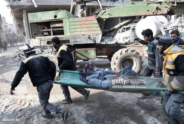 Graphic content / Volunteers from the Syrian Civil Defence carry a girl on a stretcher after digging her out of the rubble following an air strike on...