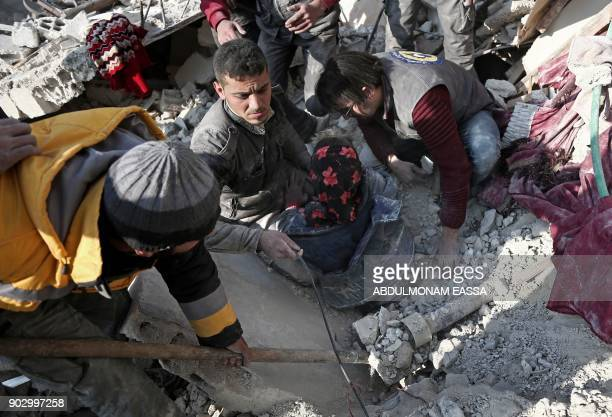 Graphic content / Volunteers from the Syrian Civil Defence dig a girl out of the rubble following an air strike on Hamouria in the besieged rebelheld...