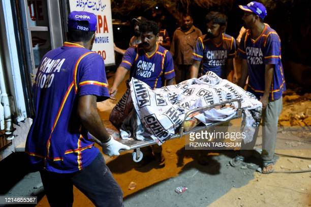 Graphic content / Volunteers transport the body of a victim to a hospital after a Pakistan International Airlines aircraft crashed in a residential...