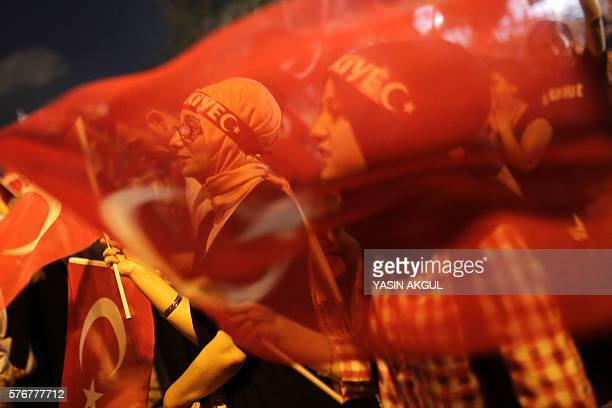 Graphic content / Women wave flags during a rally of proErdogan supporters at Taksim square in Istanbul on July 17 2016 following a failed coup...