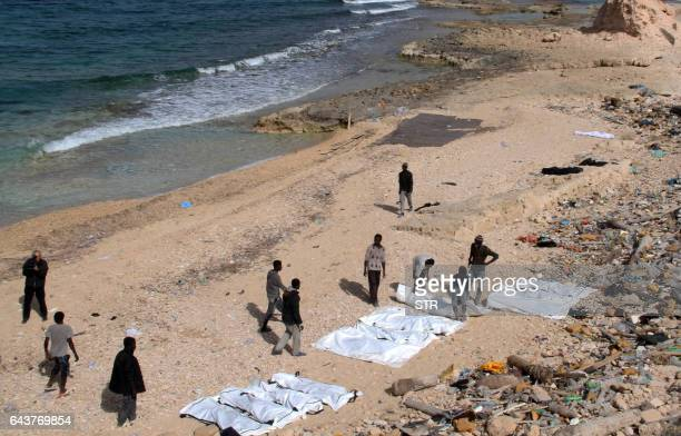Graphic content / Workers help on February 22 2017 to recover bodies of some of the 74 migrants who drowned in the Mediterranean trying to reach...