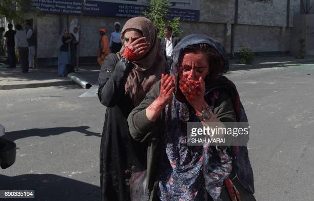 Graphic content / Wounded Afghan women gesture at the site of a car bomb attack in Kabul on May 31 2017 A massive blast rocked Kabul's diplomatic...