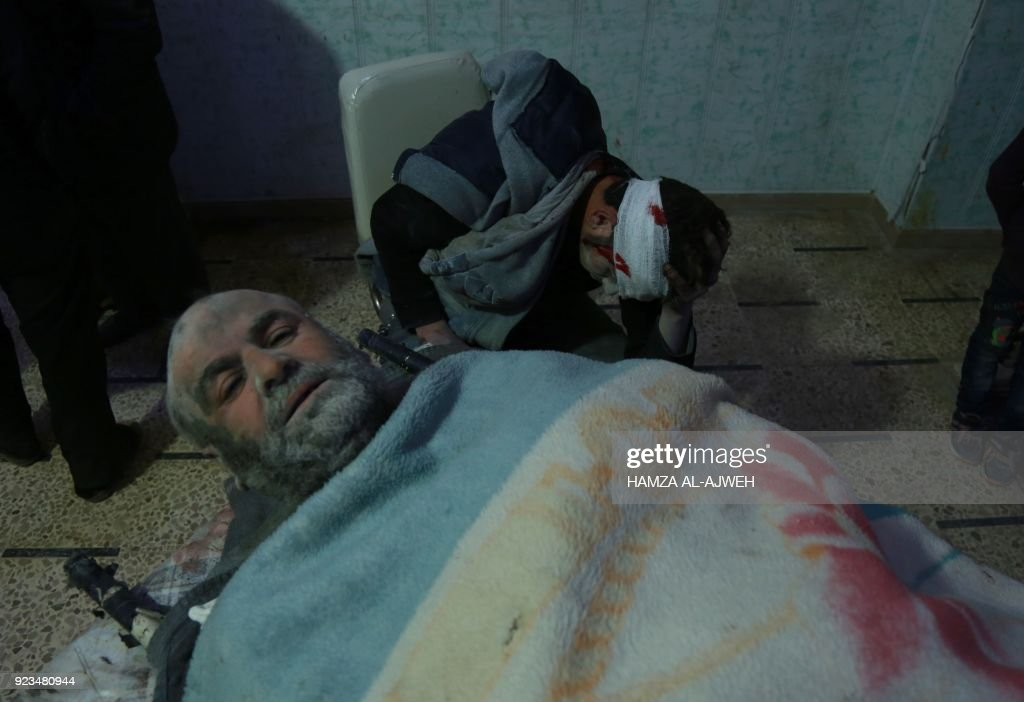 Graphic content / Wounded Syrians are pictured at a makeshift hospital in the rebel-held town of Douma, in the besieged Eastern Ghouta region on the outskirts of the capital Damascus, following air strikes by regime forces on the area on February 23, 2018. Syrian regime air strikes and artillery fire hit the rebel-held enclave of Eastern Ghouta for a sixth straight day killing dozens of civilians, as the world struggled to reach a deal to stop the carnage. /