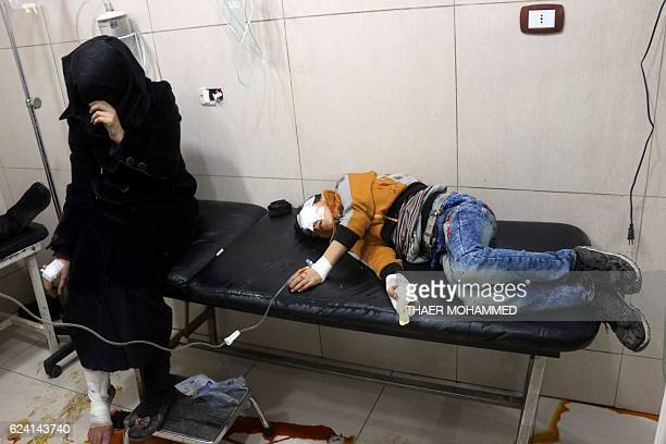 Graphic content / Wounded Syrians are seen on a table in a crowded makeshift hospital in eastern Aleppo as regime aircraft and artillery pounded...