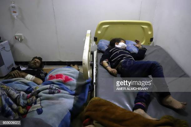 Graphic content / Wounded Syrians rest after receiving treatment at a makeshift clinic during Syrian government air strikes on Zamalka in the rebel...