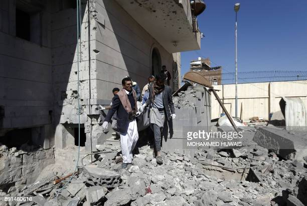 Graphic content / Yemeni Huthis carry the body of a man killed by air strikes at a detention centre in the capital Sanaa on December 13 2017 Saudiled...