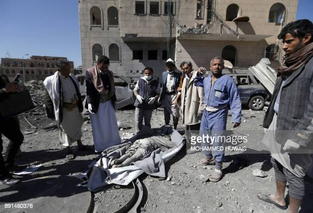 Graphic content / Yemeni Huthis gather around the body of a man killed by air strikes at a detention centre in the capital Sanaa on December 13 2017...