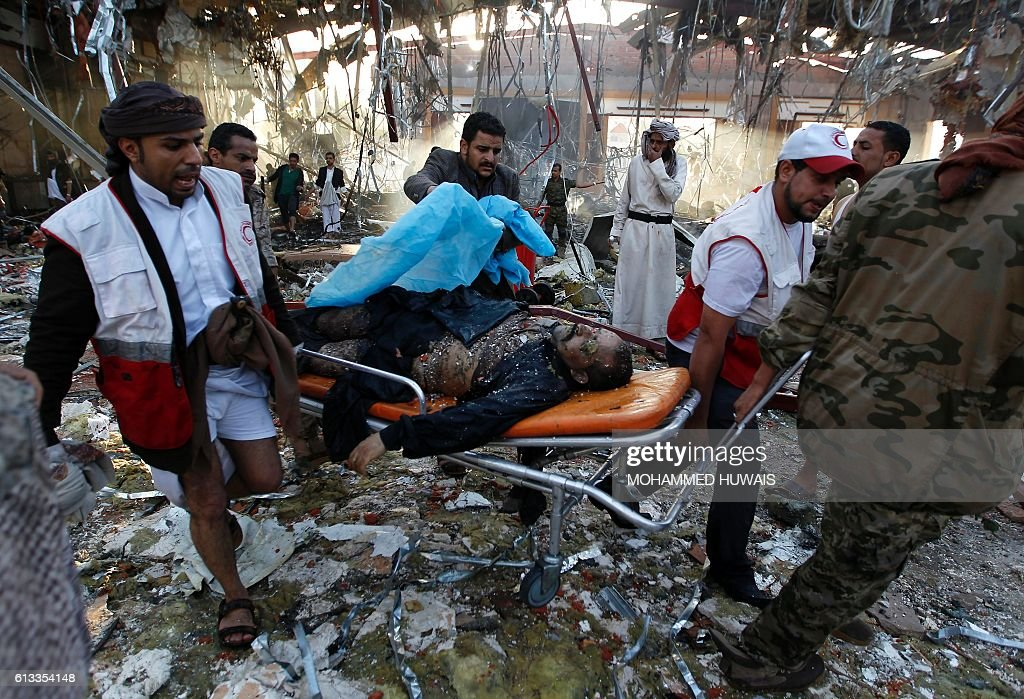 Graphic content / Yemeni Red Crescent workers carry a victim on a stretcher amid the rubble of a destroyed funeral hall building following reported airstrikes by Saudi-led coalition air-planes on the capital Sanaa on October 8, 2016. Rebels in control of Yemen's capital accused the Saudi-led coalition fighting them of killing or wounding dozens of people in air strikes on Sanaa. The insurgent-controlled news site sabanews.net said that coalition planes hit a building in the capital where people had gathered to mourn the death of an official, resulting in 'dozens of dead or wounded'. / AFP / MOHAMMED