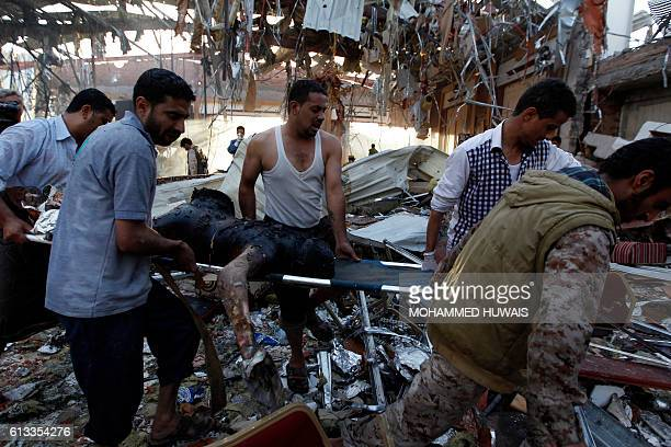 Graphic content / Yemeni rescue workers carry a charred body on a stretcher amid the rubble of a destroyed funeral hall building following reported...
