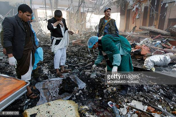 Graphic content / Yemeni rescue workers search for body parts amid the rubble of a destroyed funeral hall building following reported airstrikes by...