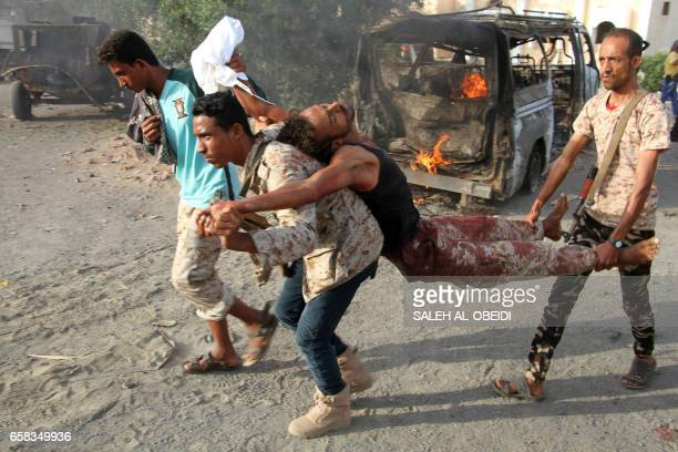 Graphic content / Yemenis carry a wounded man past a burning vehicle following a reported suicide car bombing in Huta the capital of the southern...