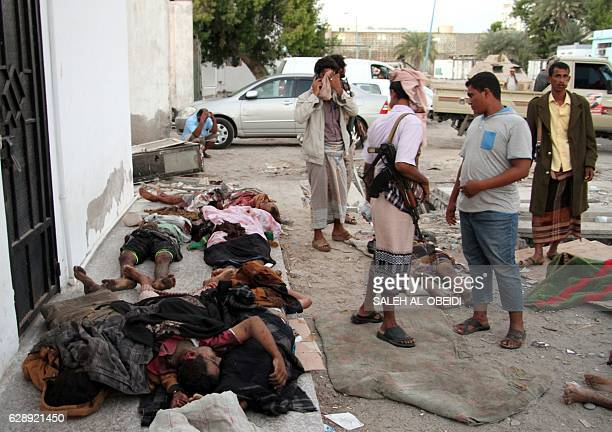 Graphic content / Yemenis gather around bodies lying covered on the ground on December 10 2016 after a suicide bomber killed 35 soldiers and wounded...