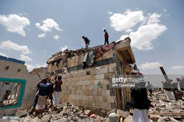 Graphic content / Yemenis look at the body of a man stuck under the collapsed roof of a building hit in an air raid in the Arhab area around 20...