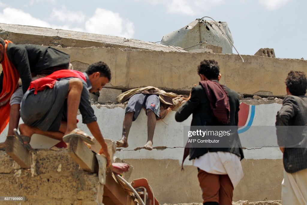 Graphic content / Yemenis look at the body of a man stuck under the collapsed roof of a building hit in an air raid in the Arhab area, around 20 kilometres (13 miles) north of Sanaa, on August 23, 2017, where a Saudi-lead coalition has been bombing Iran-backed Huthi rebels. The Huthis, who control Sanaa along with forces loyal to former president Ali Abdullah Saleh, blamed the pro-government Arab military coalition for the attack on Arhab district. / AFP PHOTO / Mohammed HUWAIS