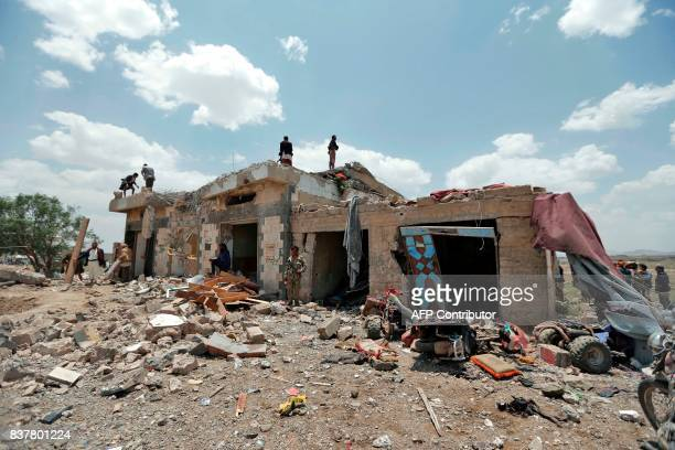 Graphic content / Yemenis stand at the site of an air raid in the Arhab area around 20 kilometres north of Sanaa on August 23 where a Saudilead...